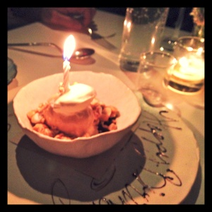 Salted caramel ice cream with candied popcorn, peanuts, whipped cream, and a lovely cursive Happy Birthday written in chocolate sauce on the plate's edge.